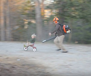 Father Uses a Leaf Blower to Push His Little Son